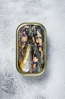 Open blik met sardine in olijfolie. witte tafel. bovenaanzicht.