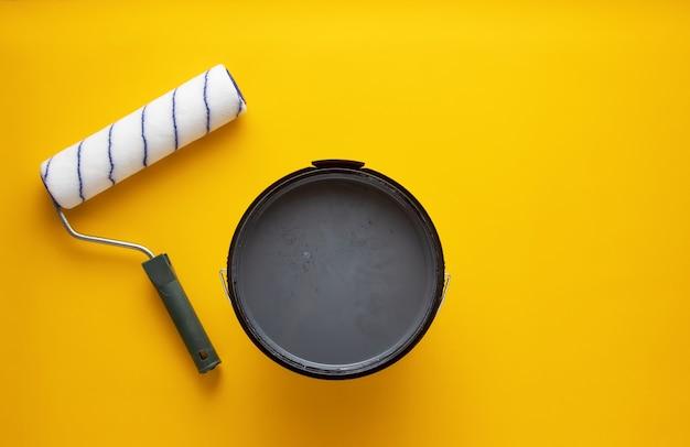 Open blikje grijze verf met een roller. home renovatie concept.