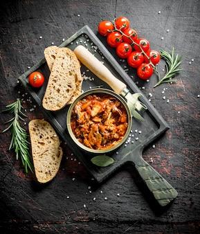 Open blikje met sprot in tomatensaus op snijplank op donkere rustieke tafel