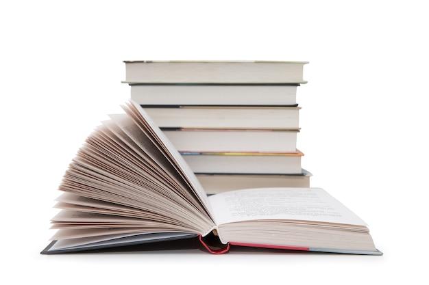 Open boek dichtbij stapel geïsoleerde boeken