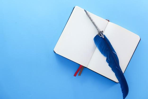 Open boek en een oude vulpen op blauwe achtergrond