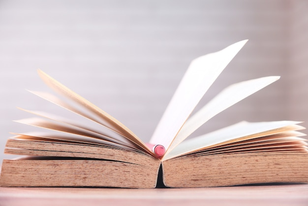 Open boek en een potlood op houten tafel