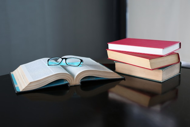 Open boek en hardcover boeken op houten tafel in de bibliotheek.