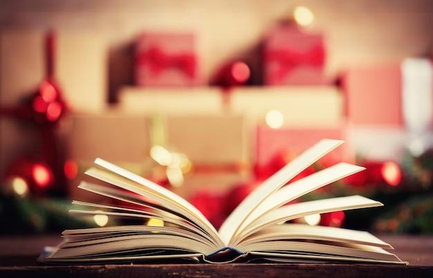 Open boek en kerstcadeau en kerstballen op achtergrond