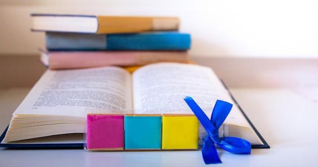 Open boek en kleurrijke boektoren bij achtergrond met tekst over internationale boekdag