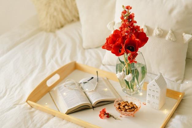 Open boek en vaas rode tulpen op een dienblad op het bed