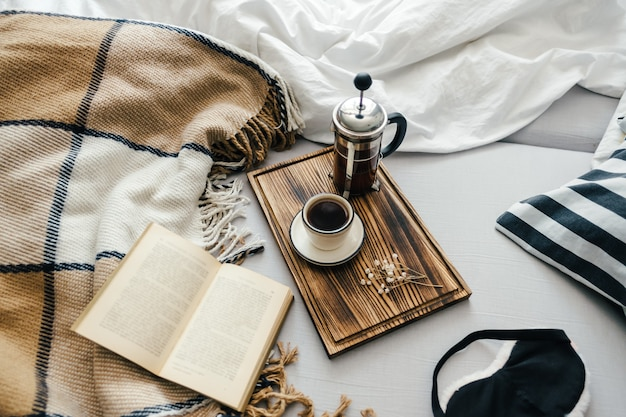 Open boek in bed met koffie gebrouwen in een franse pers en kopje op een houten bord