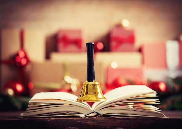 Open boek met bel en kerstcadeau en kerstballen op achtergrond