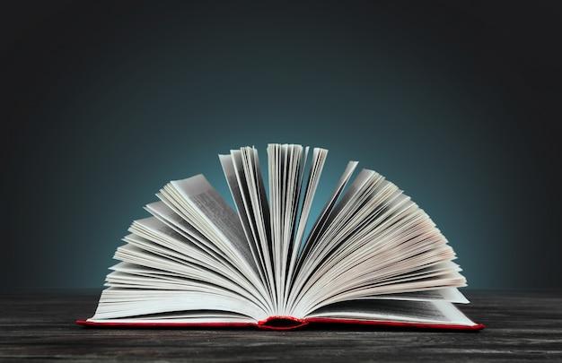 Open boek met een rode kaft op een blauwe achtergrond kopie ruimte. boek op een houten tafel.
