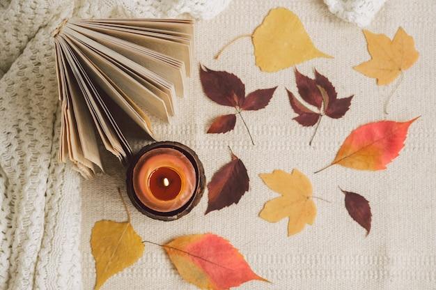 Open boek met kaarsen en bladeren