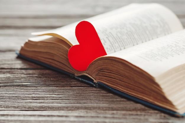 Open boek met rode hartvormige papieren bladwijzer op houten tafel