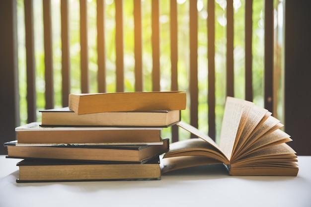 Open boek op bureau in de bibliotheekruimte dichtbij venster met vage nadruk voor achtergrond.
