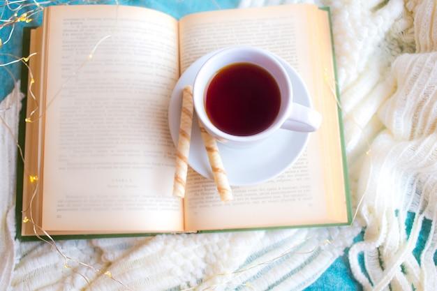 Open boek op de tafel met verlichting en koffiekopje
