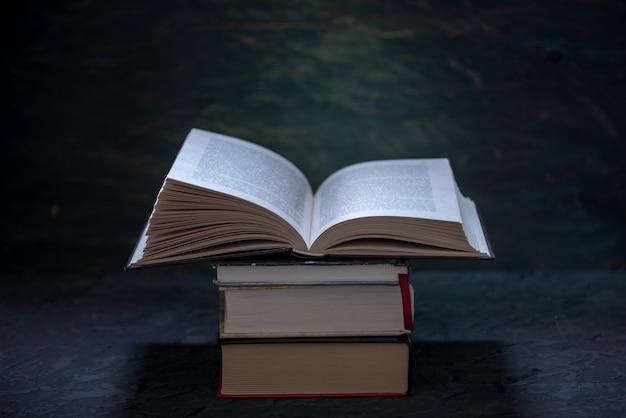 Open boek op een stapel boeken op een tafel in het donker