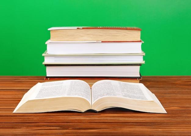Open boek op een stapel boeken op een tafel.