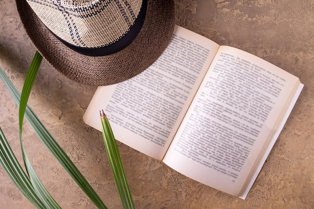 Open boek, strohoed, palmbladeren op zanderige achtergrond
