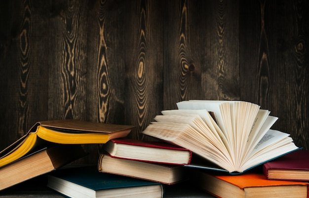 Open boeken met gele pagina's en rode kaft op een houten achtergrond kopie ruimte.
