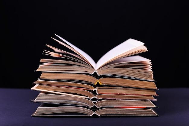 Open boeken worden gestapeld op het bureau, op een zwarte achtergrond, isoleren