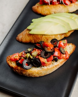 Open broodjes met appelolijven en tomaten in zwarte plaat.
