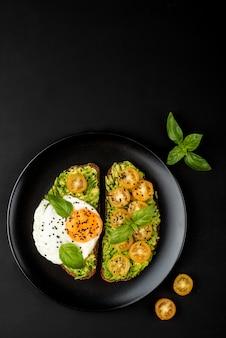Open broodjes met avocado guacamole, gele cherry tomaten, gebakken ei en basilicum op een zwarte plaat
