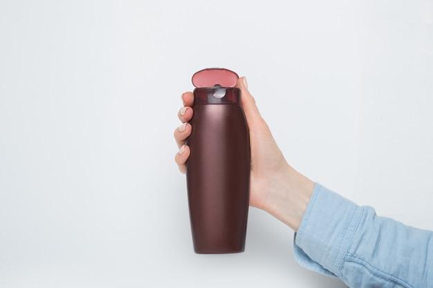 Open bruine fles voor cosmetica in een vrouwelijke hand. witte achtergrond