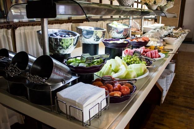 Open buffet in het hotel. gesneden watermeloen, sinaasappelen, tomaten, druiven in witte kommen