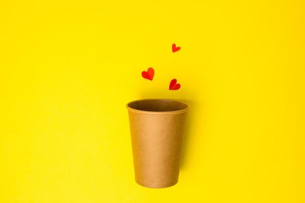 Open craft papieren beker met papieren harten op een gele achtergrond. plat liggen. creatief minimaal voedselconcept.