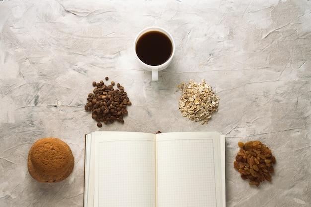 Open dagboek, koekjes, havermout, koffie, rozijnen en een kopje koffie. concept van een gezond ontbijt