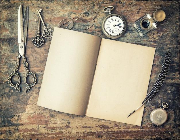 Open dagboekboek en vintage schrijfhulpmiddelen op houten tafel. verenpen, inktpotje, sleutels. getinte foto in retrostijl met vignet
