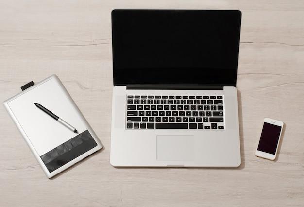 Open de laptop, grafisch tablet en smartphone op een lichttafel, bovenaanzicht
