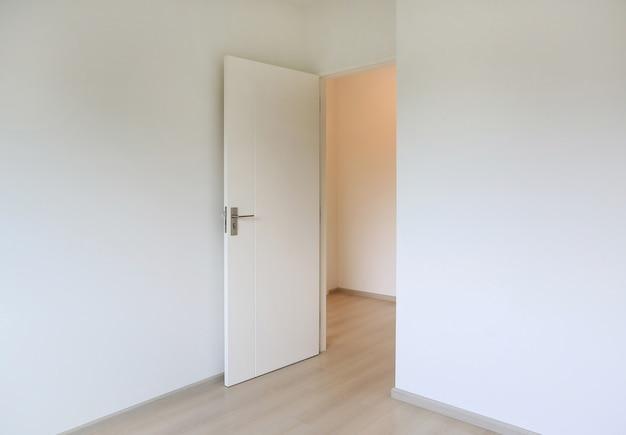 Open deur in de witte kamer van een nieuw huis