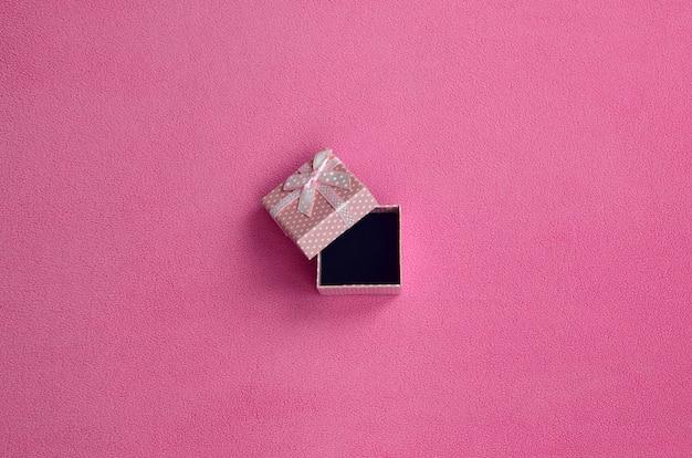 Open een klein geschenkdoosje in het roze met een strikje op een deken