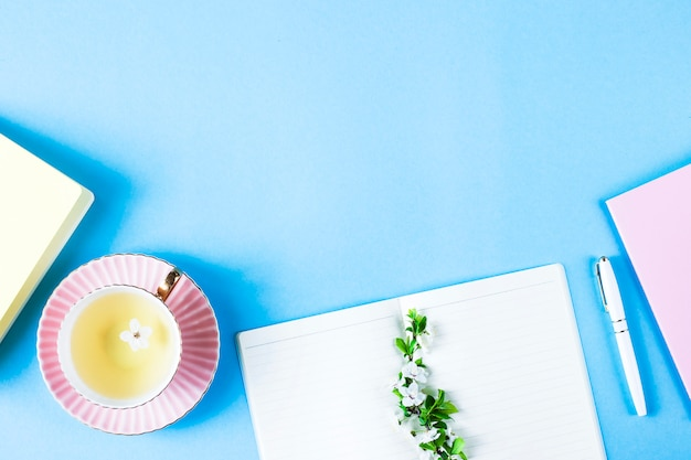 Open een notitieboek met een pen naast de bloeiende takken en een kopje thee