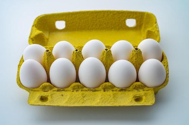 Open eierdoos met tien eieren die op witte achtergrond worden geïsoleerd