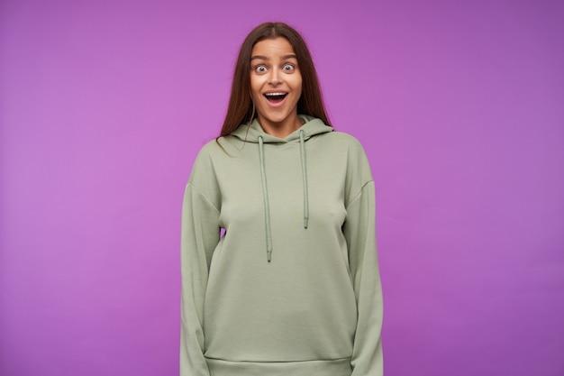 Open-eyed jonge bruinharige vrouw met natuurlijke make-up die verrast haar wenkbrauwen optrekt terwijl ze verbaasd kijkt met wijd open mond, geïsoleerd over paarse muur