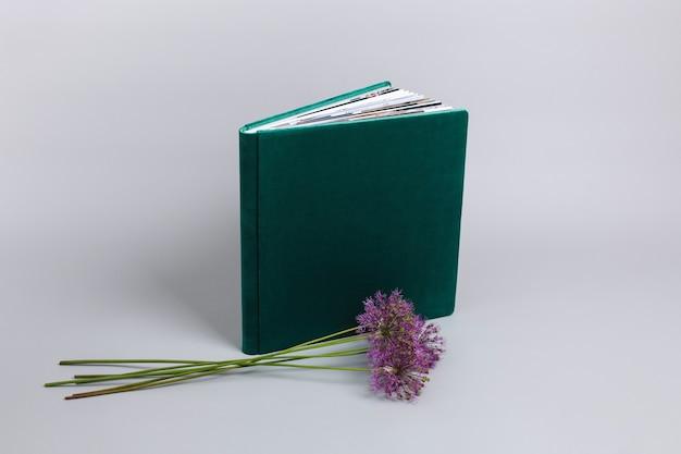 Open familiefotoboek met stijlvolle stoffen kaft geïsoleerd op een grijze achtergrond met kopie