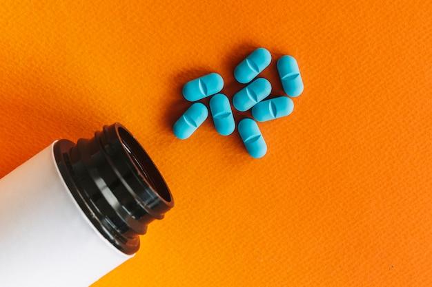Open fles dichtbij blauwe pillen op oranje achtergrond