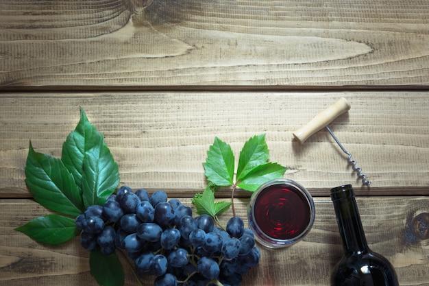 Open fles rode wijn met een glas, kurkentrekker en rijpe druif op een houten bord.