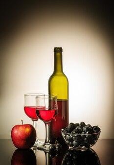 Open fles rode wijn twee glazen een appel en een beker met druiven die op een tafel staan