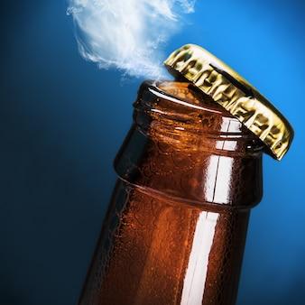 Open flesje bier op een blauw