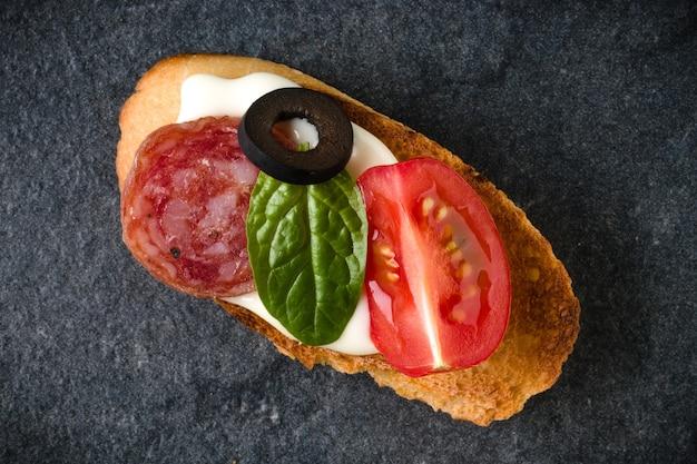 Open geconfronteerd sandwich canapé of crostini op donkere stenen close-up als achtergrond. bovenaanzicht.