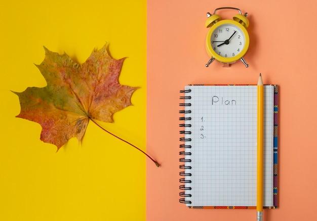Open geruit notitieboekje, geel herfst esdoornblad, bovenaanzicht plat gelegd.