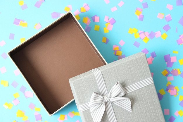 Open geschenkdoos en confetti op een gekleurde achtergrond bovenaanzicht