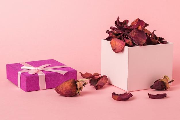 Open geschenkdoos met bloemblaadjes en toppen van gedroogde rozen