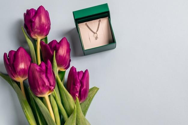 Open geschenkdoos voor sieraden met een ketting en hanger gemaakt van zilver en frisse heldere paarse tulpen op een lichtblauwe achtergrond met vrije ruimte voor tekst. overhead plat leggen