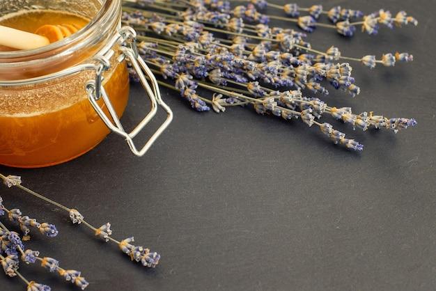 Open glazen pot met vloeibare honing en honingdipper binnenin en bosje droge lavendel op een donkere ondergrond