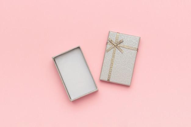 Open grijze geschenkdoos met strik op roze pastel achtergrond in minimalistische stijl mockup
