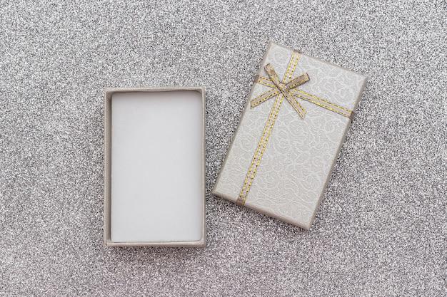 Open grijze geschenkdoos met strik op zilveren glanzende achtergrond.