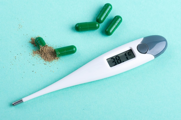 Open groene capsulepil met kruiden en thermometer op groen