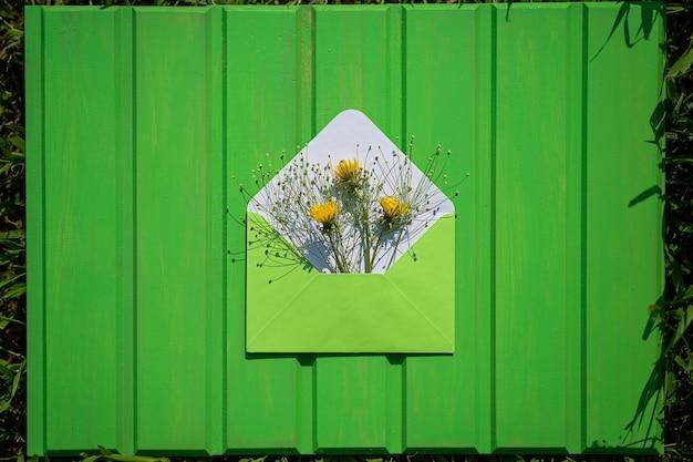 Open groene envelop met wilde bloemen op een groene houten achtergrond hallo vanaf de zomer